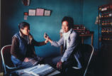 Tibetan Female Doctor Taking Pulse of Man with White Scarf